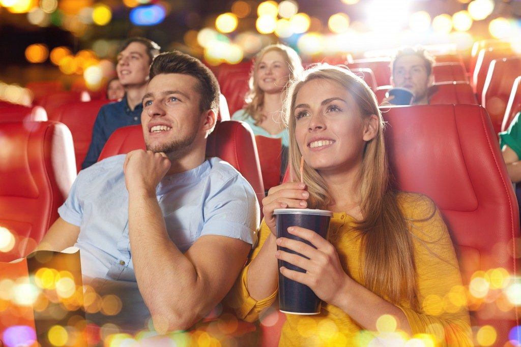 Happy friends watching a film in the theatre