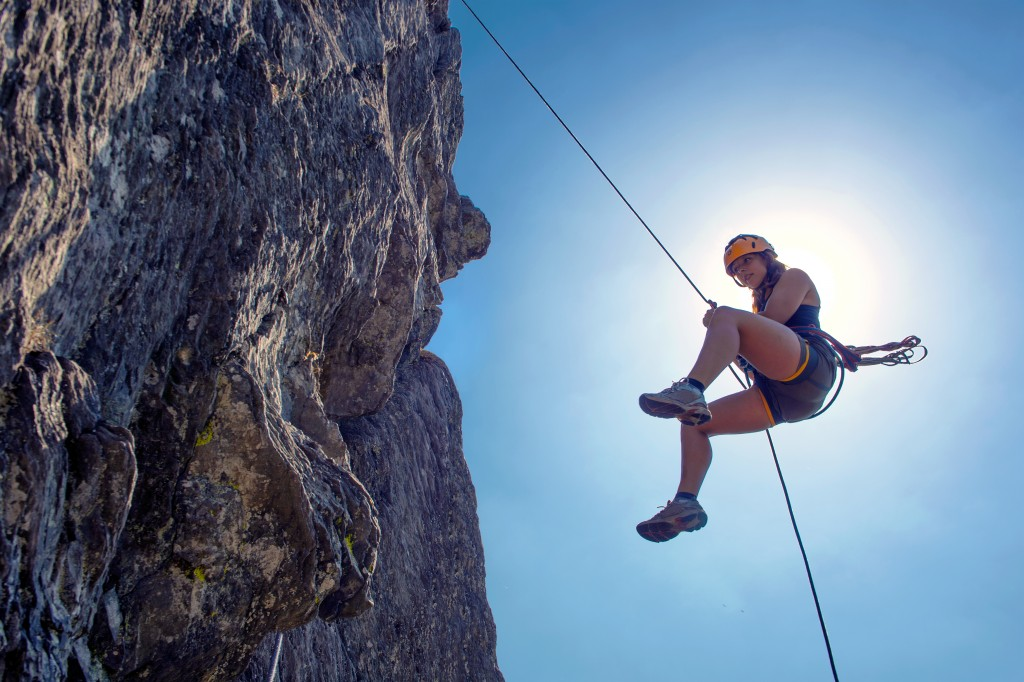 Young, tough, woman, abseiling from a steep rock, just in front of the sun
