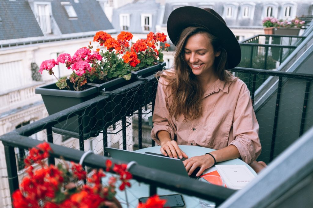 woman working remotely at her balcony