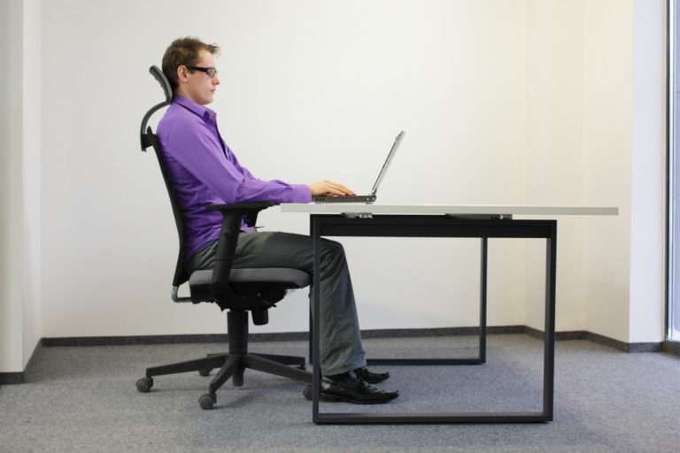 man doing work on his computer while sitting on a chair