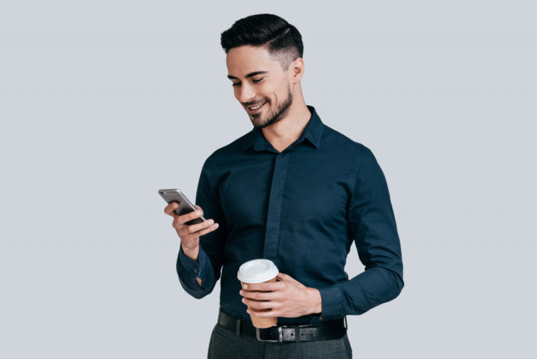 a person holding a phone and a cup of coffee