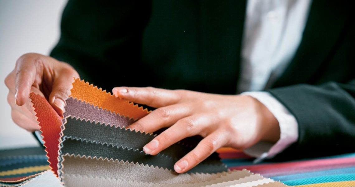 businessperson holding swatches of leathers