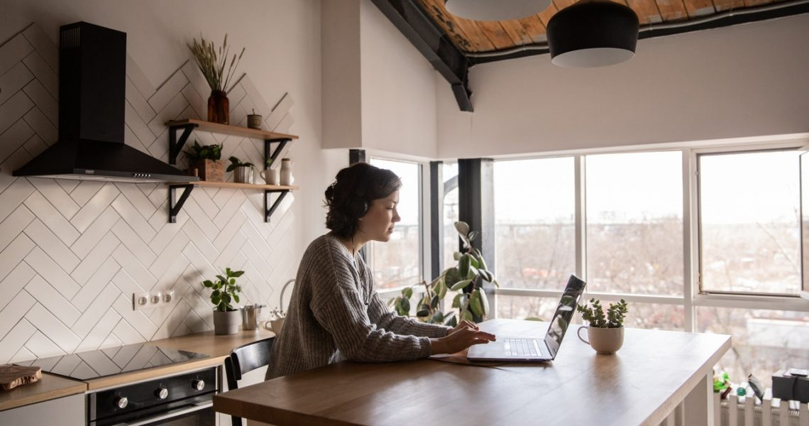 woman working remotely at her kitchen